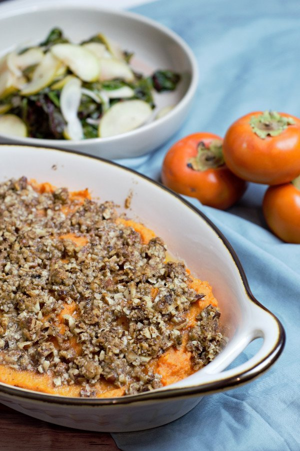 sweet potato casserole is white casserole dish on the table with sauteed greens