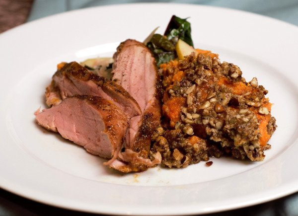 Sweet potato casserole on a white plate with cooked greens and pork loin.