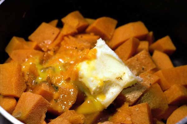 Boiled sweet potatoes with butter, egg, cream, and spices ready for mashing.