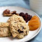 three oatmeal breakfast cookies on a plate with a side of dried fruit and a glass of milk