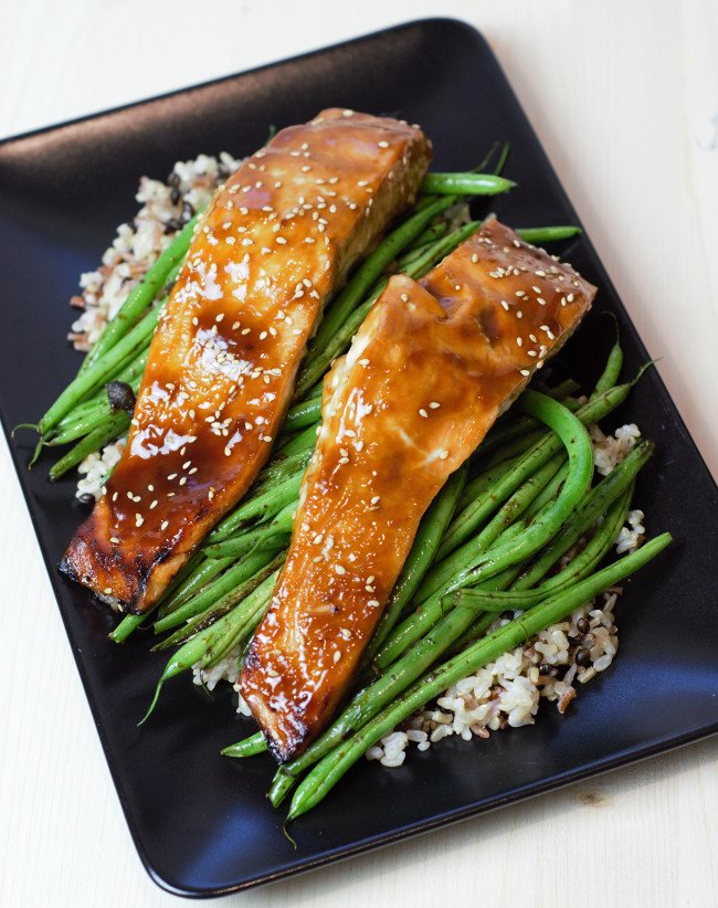 Two pieces of salmon with sticky teriyaki glazed sitting atop green beans and brown rice.