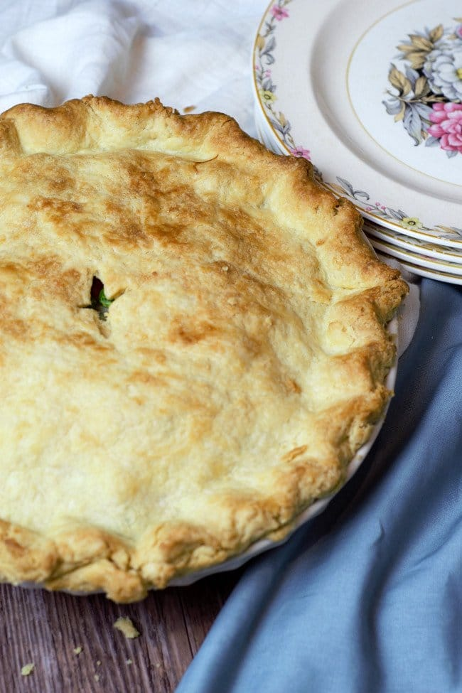 Baked chicken pot pie with plates ready to serve.