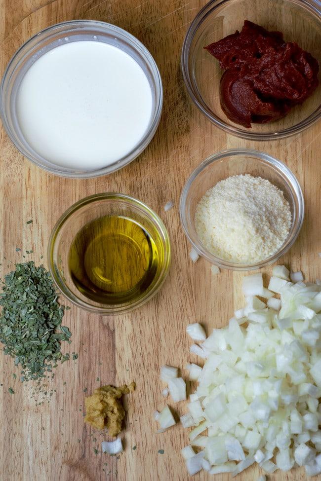 Ingredients for recipe on a cutting board. Cream, tomato paste, onion, garlic, olive oil, oregano, parmesan cheese