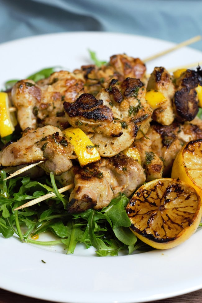 White plate with greens with stack of cooked chicken skewers on top.