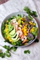 large gray bowl of shrimp salad with avocado, mango, red onion, and corn toppings on white linen background