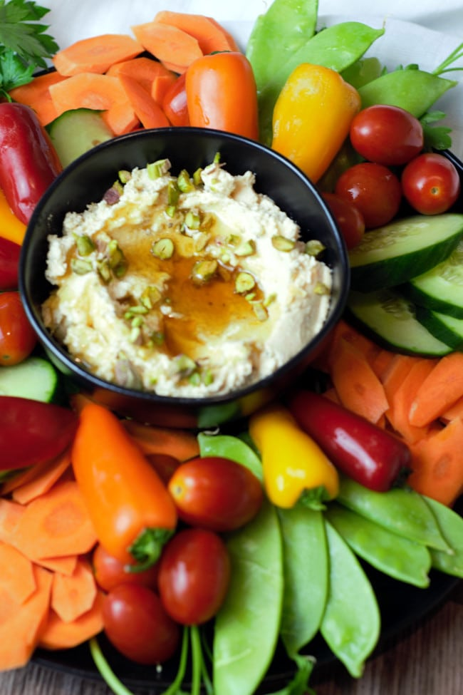 Close up of whipped feta dip in a black bowl with vegetables surrounding it.