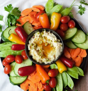 Whipped feta in black bowl surrounded by vegetables