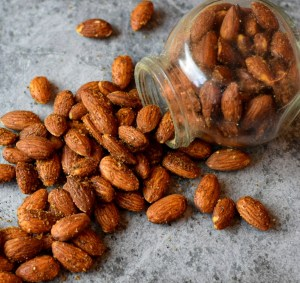 seasoned almonds spilled out of jar on marble