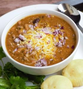 chili con carne in white bowl side of corn bread