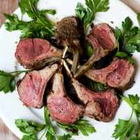 overhead shot of carved rack of lamb on white plate