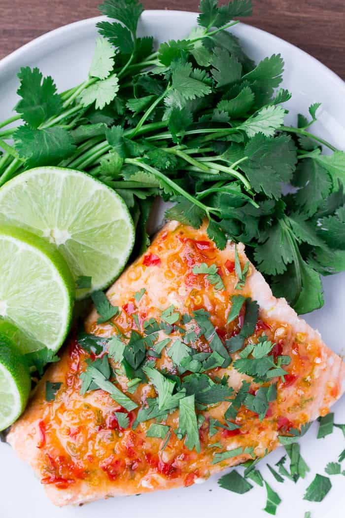 Overhead of Chili Lime Salmon Recipe on a Plate with Limes and Cilantro