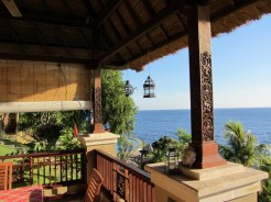 The balcony overlooking a lush garden, the pool and the open sea
