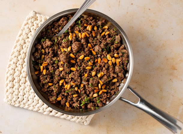 Fry pan fill with spiced ground meat and pine nuts
