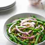 mung beans, green beans, green pea salad with pickled onion in a white bowl, three white plate and two glasses in the back ground