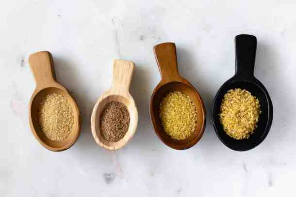 four wooden spoons filled with bulgur of different coarse grade