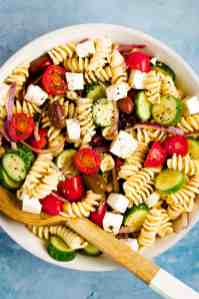 White bowl filled with greek pasta salad and a wooden salad spoon