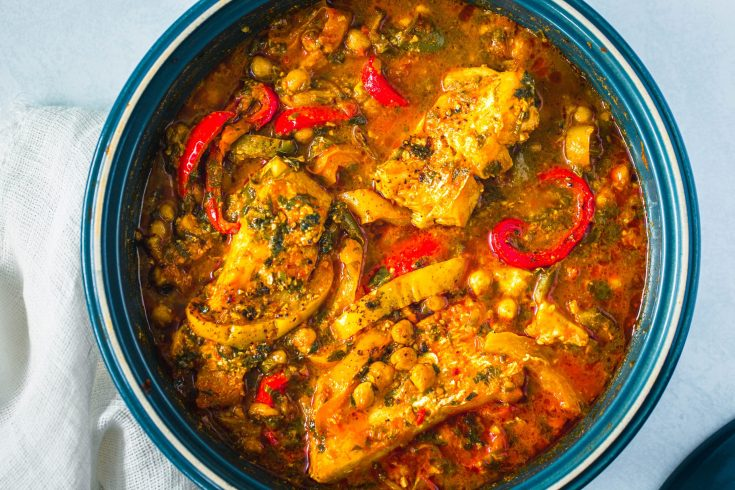 close up of fish braised in tomatoes and peppers