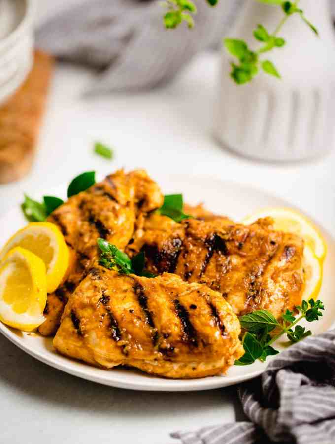 grilled greek marinated chicken breast on a white plate with styled background