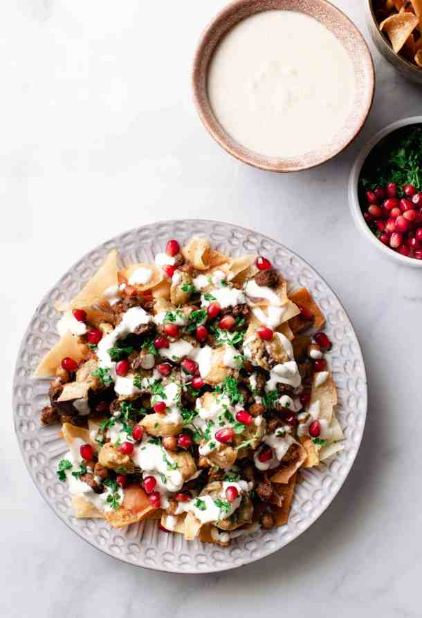 A decorative plate filled with Beef & Eggplant Fatteh, on a bed of pita chips