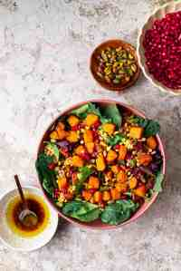 a bowl of roasted squash salad and garnishes of pomergrantes, pistachios, and date dressing