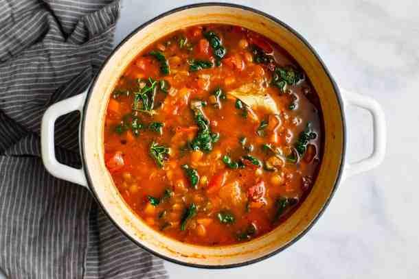 A white enamel cast iron pot of mediterranean lentil soup