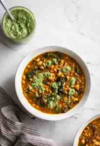 A bowl of black eyed pea soup and herb pesto
