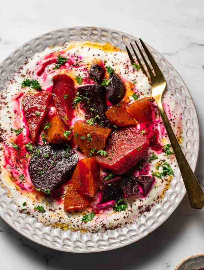 A plate filled with roasted beets and strained yogurt