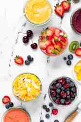 6 chia pudding parfaits in glasses jars some topped with fresh fruit others topped with fruit puree