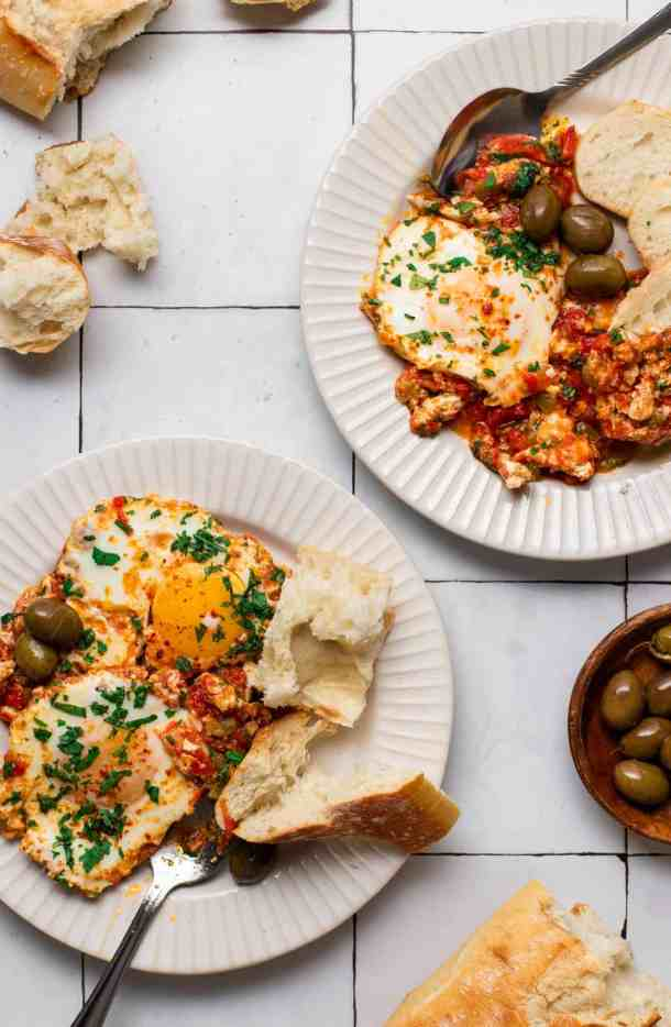 two plates of shakshuka and ripped bread with a wooden plate of green olives