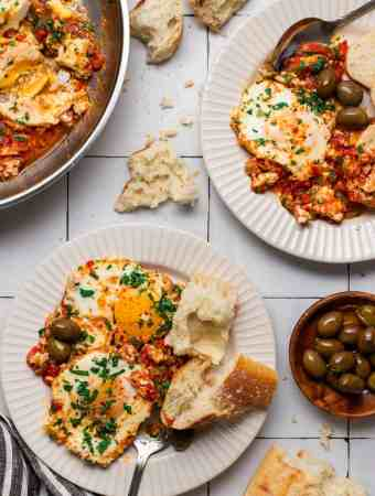 two plates fill with shakshuka, bead and olives side of olives bread and a pan with shakshuka
