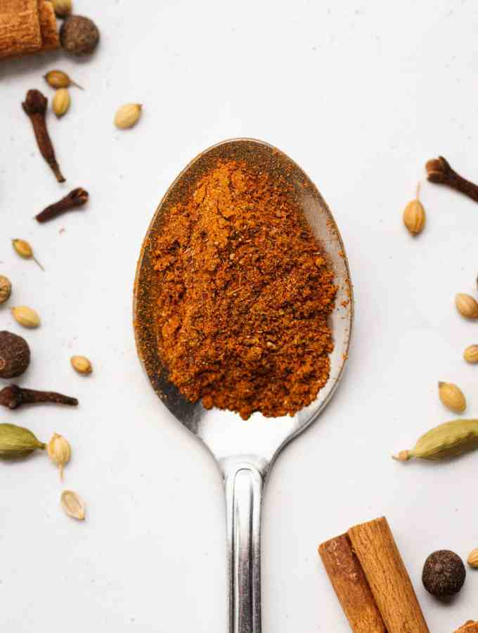 a spoon with homemade spice blend surrounded by spices