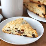 Coconut Raisin Vegan Scones fresh out of the oven and sitting on a plate with a mug of tea in the background.