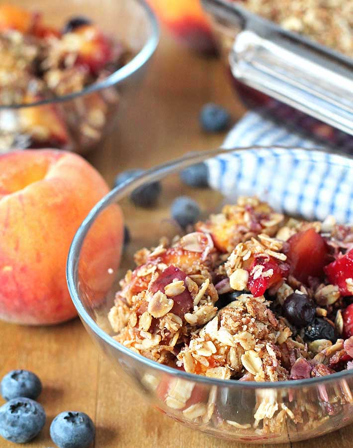 An up close shot of Vegan Peach Blueberry Crisp in a small glass bowl with fresh peaches and blueberries on the side