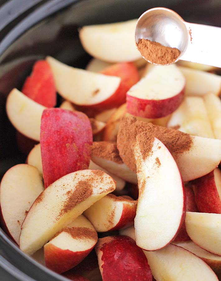 Freshly cut apples in a slow cooker with cinnamon being sprinkled on them to prepare them to make slow cooker applesauce