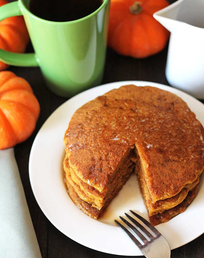 An overhead shot of a stack of vegan gluten free pumpkin pancakes on a plate with a fork sitting on the side