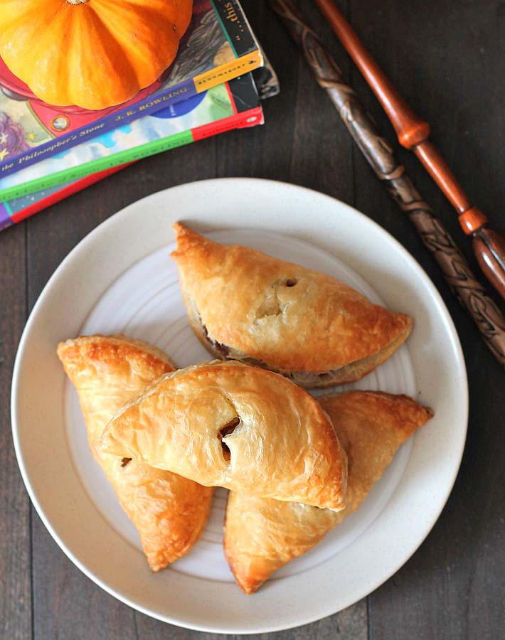 Overhead shot of four pumpkin pasties on a white plate with magic wands sitting off to the right and three Harry Potter books are behind the plate.
