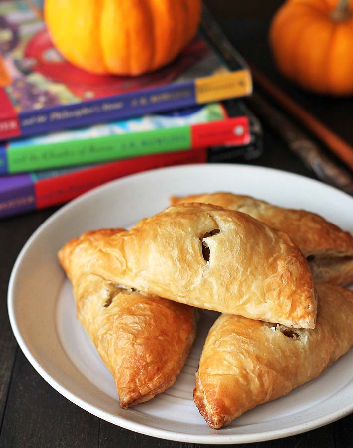 An up close shot of pumpkin pasties sitting on a plate with mini pumpkins and three Harry Potter books sitting behind the plate.