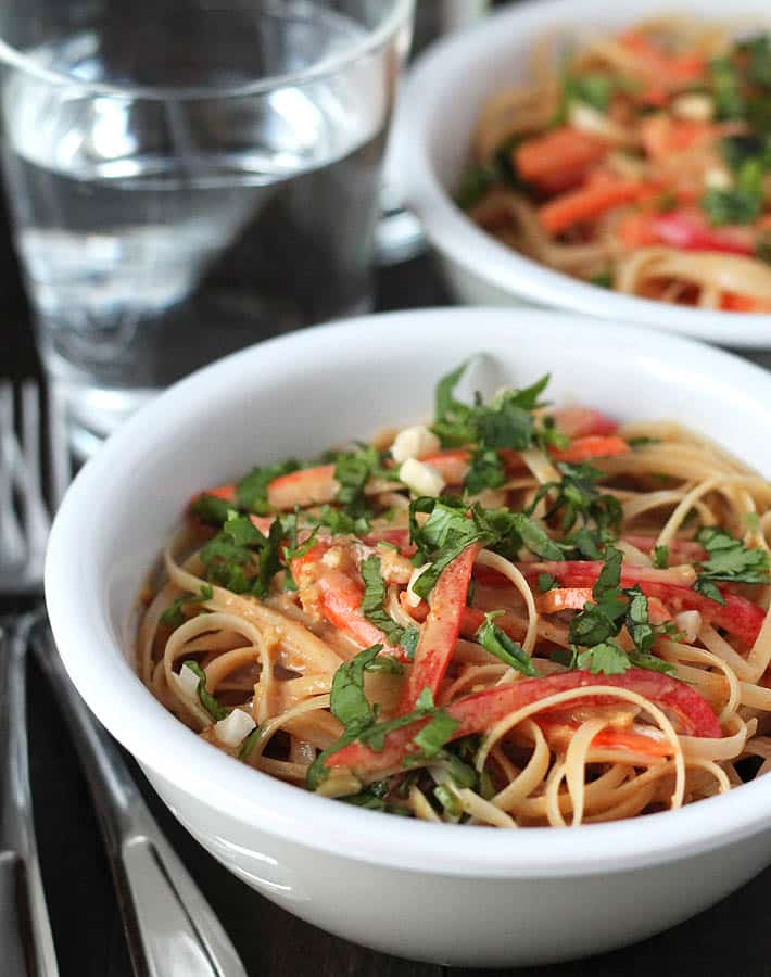 Two bowls of vegan peanut noodles sitting on a dark wooden table with two forks and two glasses of water to the left.