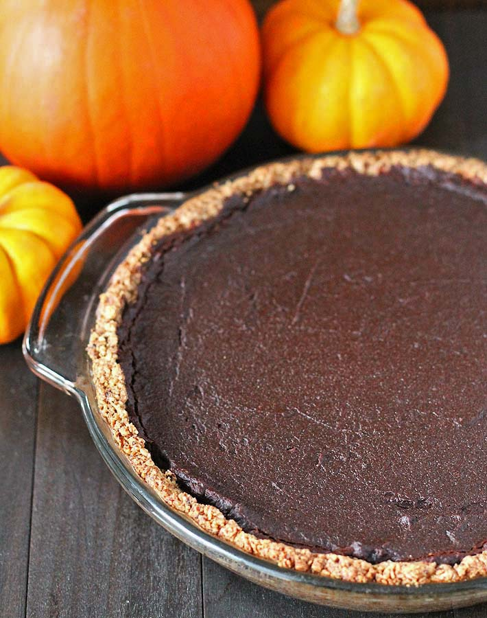A whole vegan chocolate pumpkin pie just out of the oven, sitting on a black wooden table with pumpkins behind the pie.