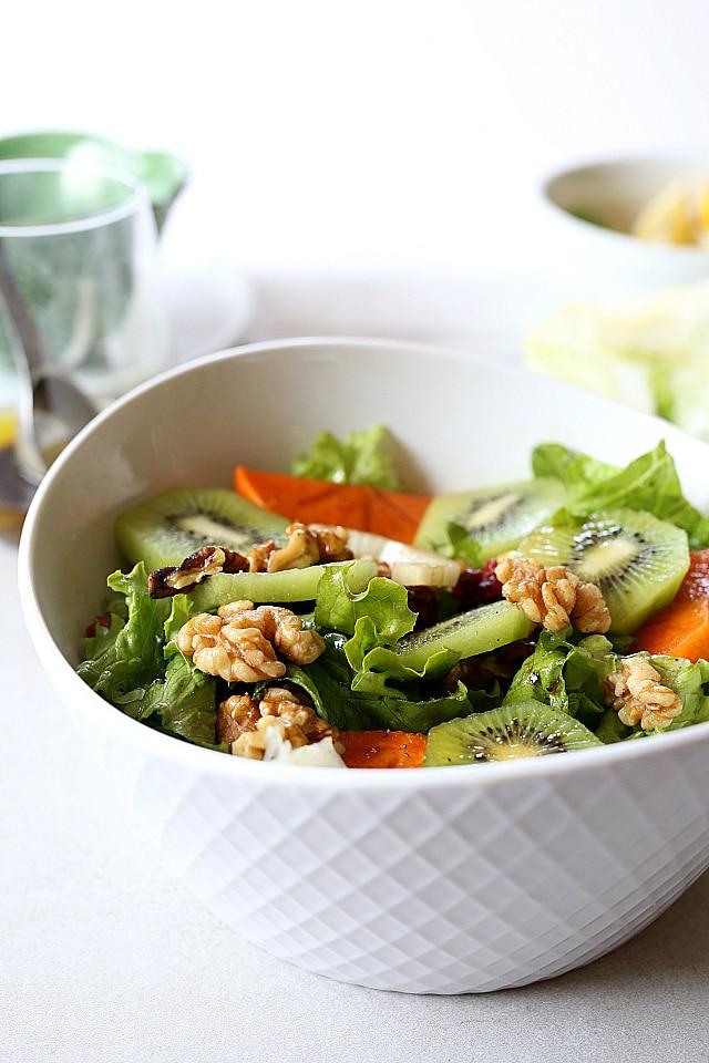 Kiwi, Persimmons, Walnuts and Cranberry greens salad in a walnut vinaigrette dressing