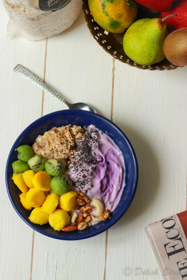 Top view of mango and kiwi scoops with easy overnight oats with blueberry yoghurt in a blue bowl