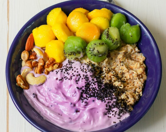 closeup view of overnight oats with blueberry yoghurt in a blue bowl