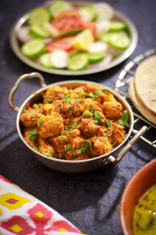 cauliflower curry served in a serving bowl on dinner table