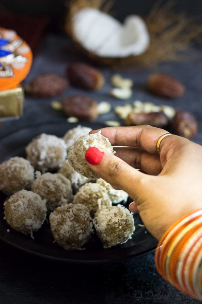 Hand with orange bangles picking up raw, vegan coconut date balls
