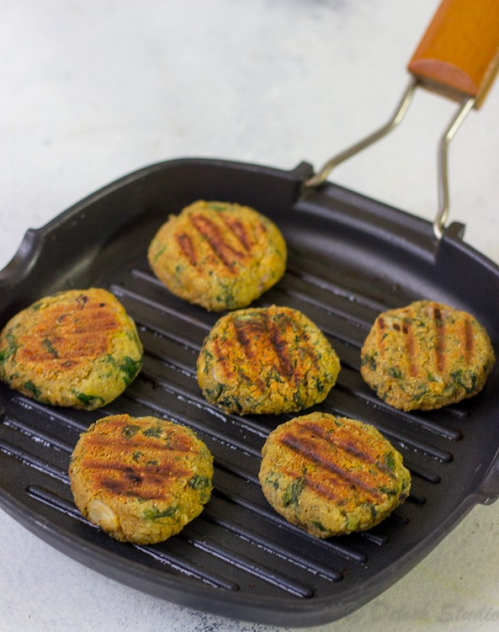 Quinoa cutlets or quinoa patties being grilled on a skillet.