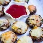 Baked cheese stuffed mushrooms served as vegetarian appetiser.