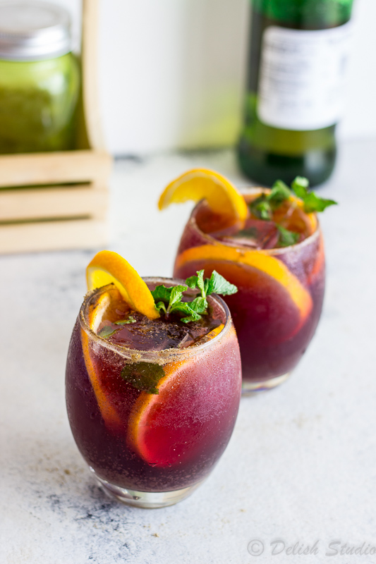 A side shot of Jaljeera red wine sangria cocktail with wine bottle at the back. Jaljeera mixed with the goodness of Red wine Sangria is what makes up this tangy, boozy, fizzy refreshing summer cocktail! Super easy to make this is recipe gives an Indian twist to classic Red wine Sangria!
