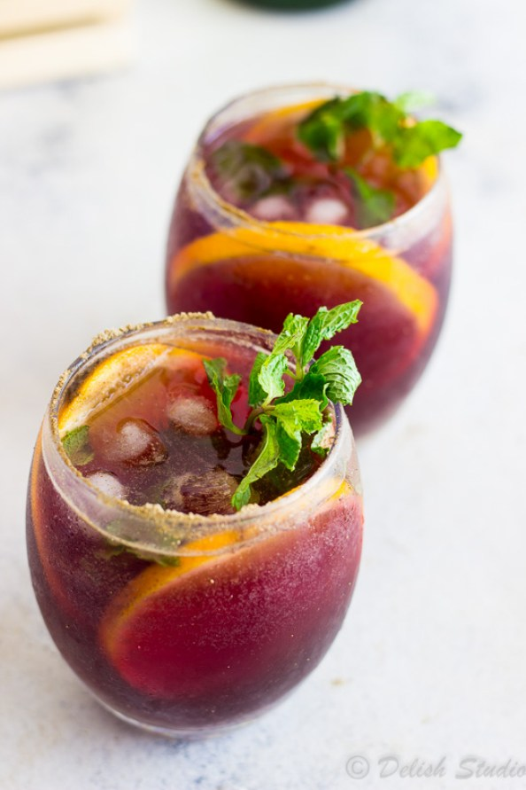 Close up image of 2 glasses of Jaljeera mixed with the goodness of Red wine Sangria is what makes up this tangy, boozy, fizzy refreshing summer cocktail! Super easy to make this is recipe gives an Indian twist to classic Red wine Sangria!