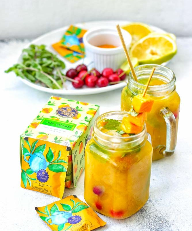 Aam Salaam mango iced tea mocktail in two mason jars with fresh fruits and mangoes