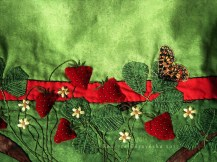 Stuffed, appliqued velvet strawberries with green seed beads, appliqued and embroidered leaves and flowers.